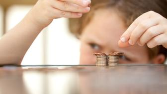 little girl counting coins from pocket money on the table