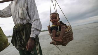 TEKNAFF, BANGLADESH - SEPTEMBER 12 : A Rohingya Muslim man, fled from ongoing military operations in Myanmars Rakhine state, carries his child with a basket attached to a wooden stick as they fled Bangladesh by boat over sea in Teknaff, Bangladesh on September 12, 2017.   (Photo by Zakir Hossain Chowdhury/Anadolu Agency/Getty Images)