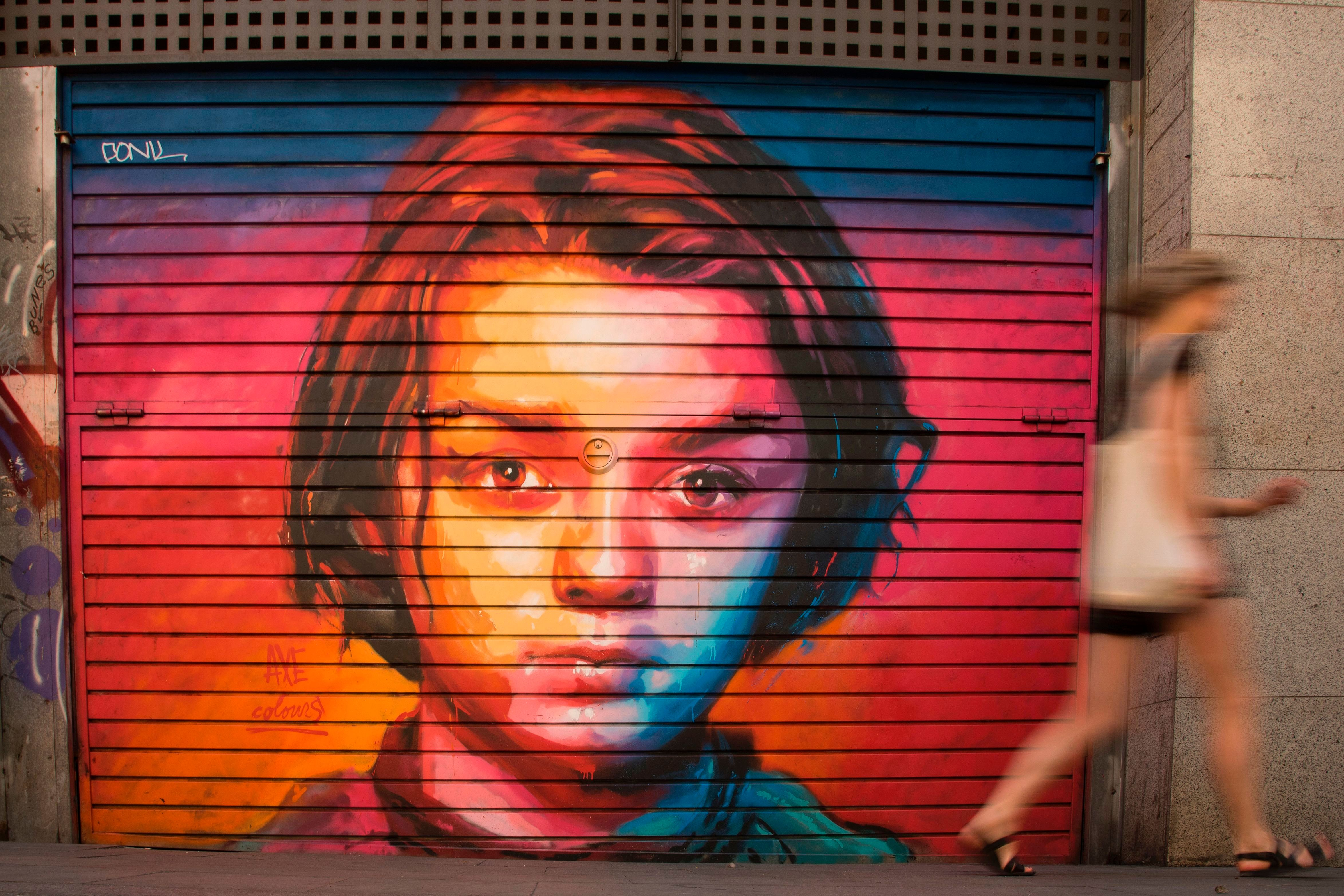 A woman walks in front a graffiti by street artist 'Axe Colours' portraying British actress Maisie Williams known for playing Arya Stark in The Game of Thrones TV series, in Barcelona  on July 30, 2017. / AFP PHOTO / Josep LAGO        (Photo credit should read JOSEP LAGO/AFP/Getty Images)