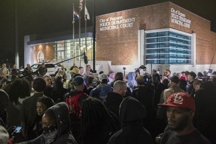 Protestors gather in front of the Ferguson Police Department after the Justice Department released their report exposing corr