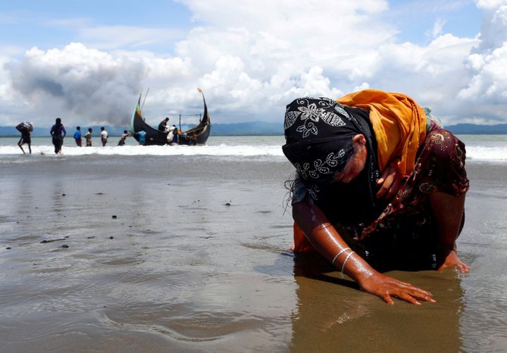An exhausted Rohingya refugee woman touches the shore after crossing the Bangladesh-Myanmar border by boat on Sept. 11,