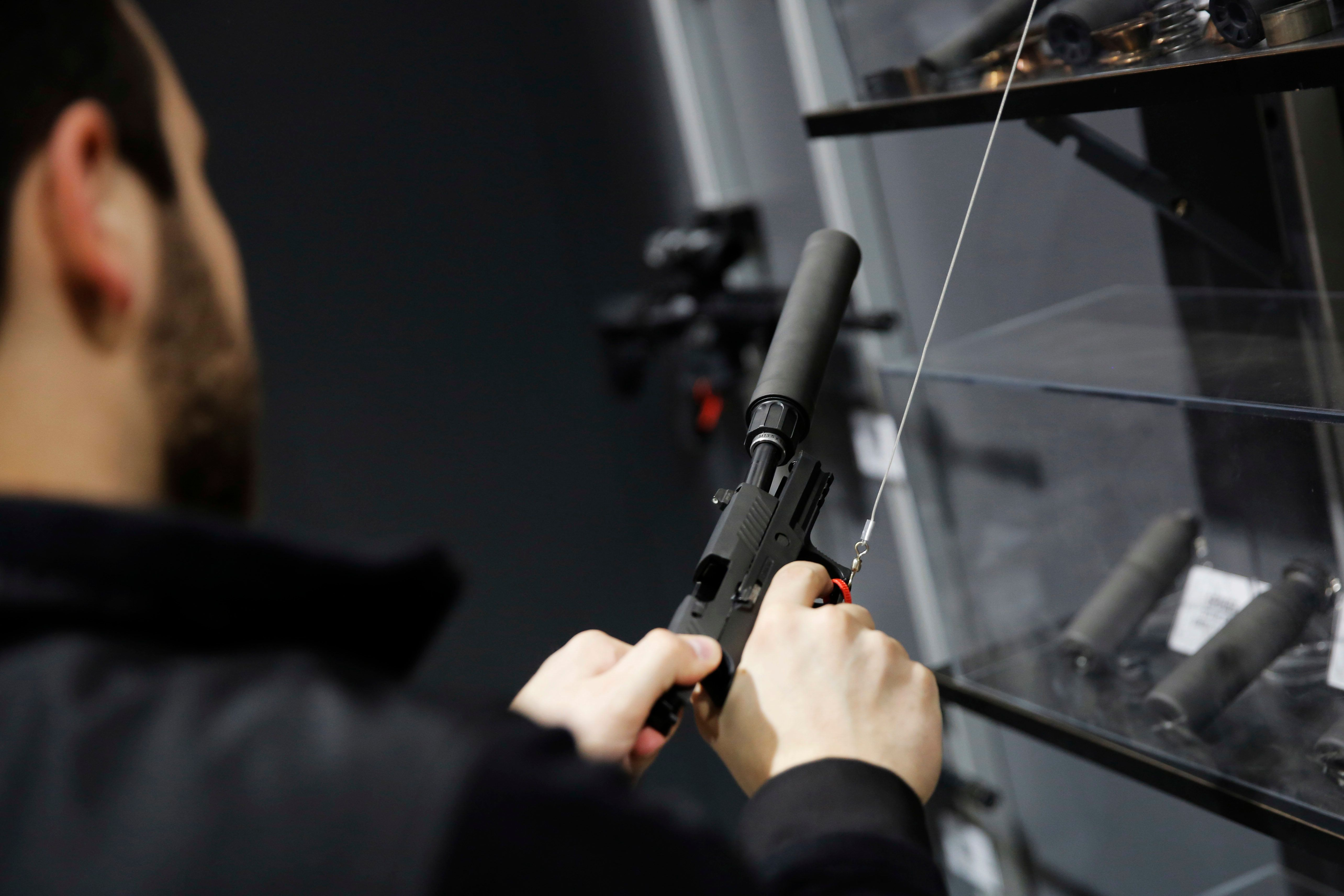 A visitor pulls the slide of a pistol with a silencer at a National Rifle Association outdoor sports trade show on Feb. 10, 2