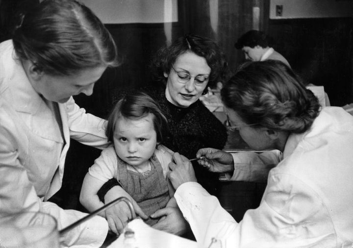 A rather reluctant-looking girl receives the polio vaccine in Britain in 1956.