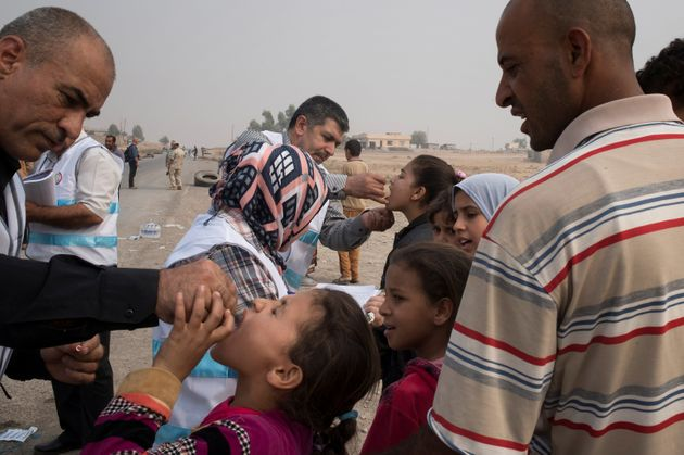 Displaced children, who fled villages south of Mosul, Iraq, receive drops of oral polio vaccine from...