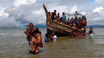 Smoke is seen on Myanmar's side of border as Rohingya refugees get off a boat after crossing the Bangladesh-Myanmar border through the Bay of Bengal in Shah Porir Dwip, Bangladesh September 11, 2017. REUTERS/Danish Siddiqui