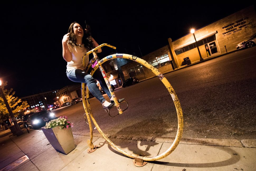 Reporter Jenna Amatulli rides a bike sculpture in front of the HandleBar.