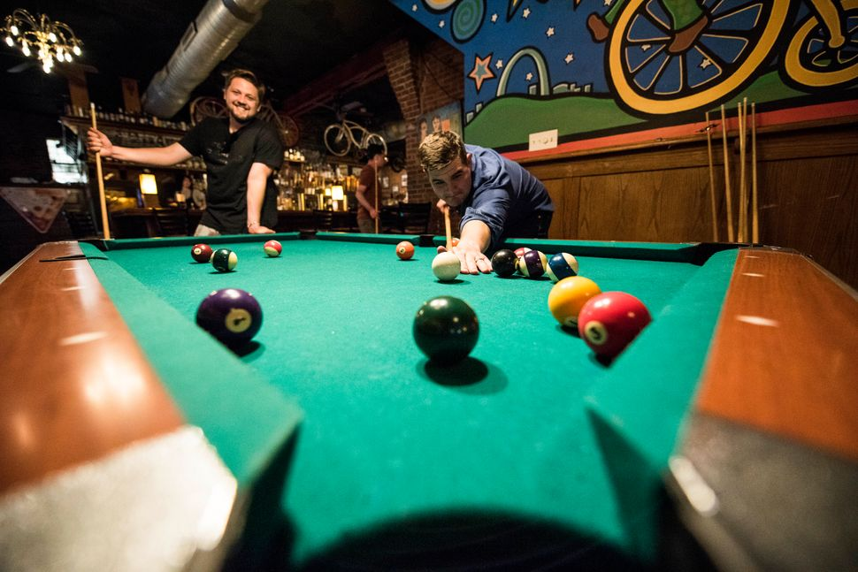 HuffPost staff play pool at the HandleBar in St. Louis.