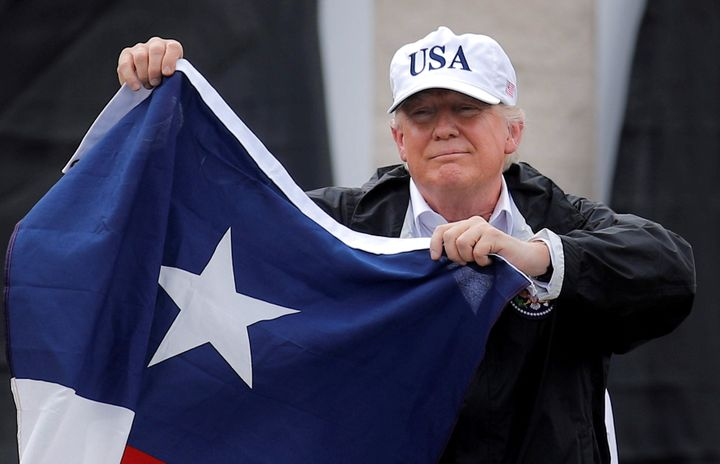 President Donald Trump holds the Texas flag after receiving a briefing on Tropical Storm Harvey relief efforts in Corpus Chri