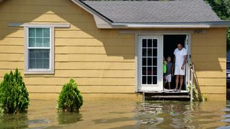 A family stand in the door of their flooded house in Port Arthur, Texas, U.S., August 31, 2017. REUTERS/Carlo Allegri