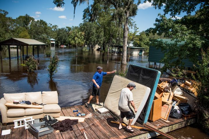 Marc St. Peter, left, and Chris Wisor lend a hand cleaning up as floodwaters from Hurricane Irma recede Wednesday in Middlebu