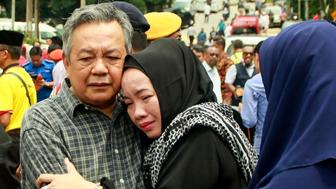 Nik Azlan Nik Abdul Kadir (L), father of one of the victims comforts his wife outside the Darul Quran Ittifaqiyah religious school in Kuala Lumpur on September 14, 2017. Twenty-four people, mostly teenage boys, were killed on September 14 when a blaze tore through a Malaysian religious school, in what officials said was one of the country's worst fire disasters for years. / AFP PHOTO / SADIQ ASYRAF        (Photo credit should read SADIQ ASYRAF/AFP/Getty Images)