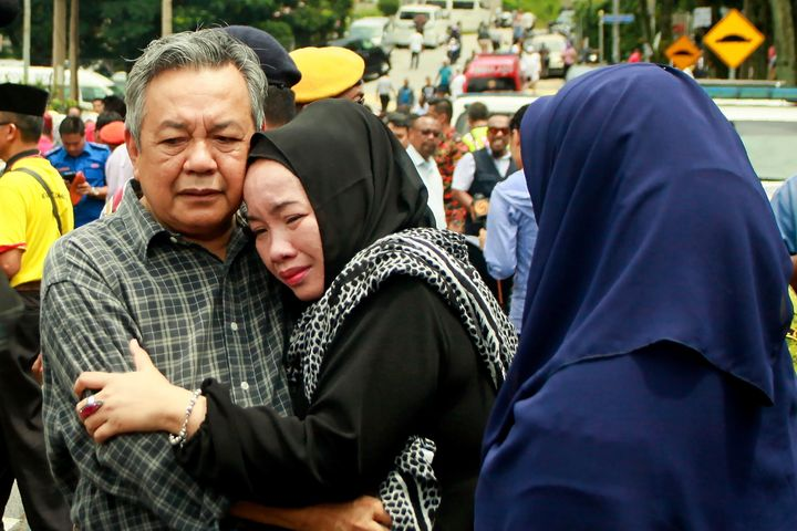 Nik Azlan Nik Abdul Kadir, left, father of one of the victims, comforts his wife after a deadly fire at their child's religio