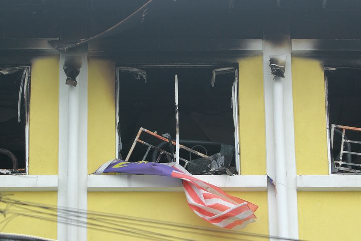A Malaysian national flag flutters outside the burnt windows of the Darul Quran Ittifaqiyah religious school in Kuala Lumpur