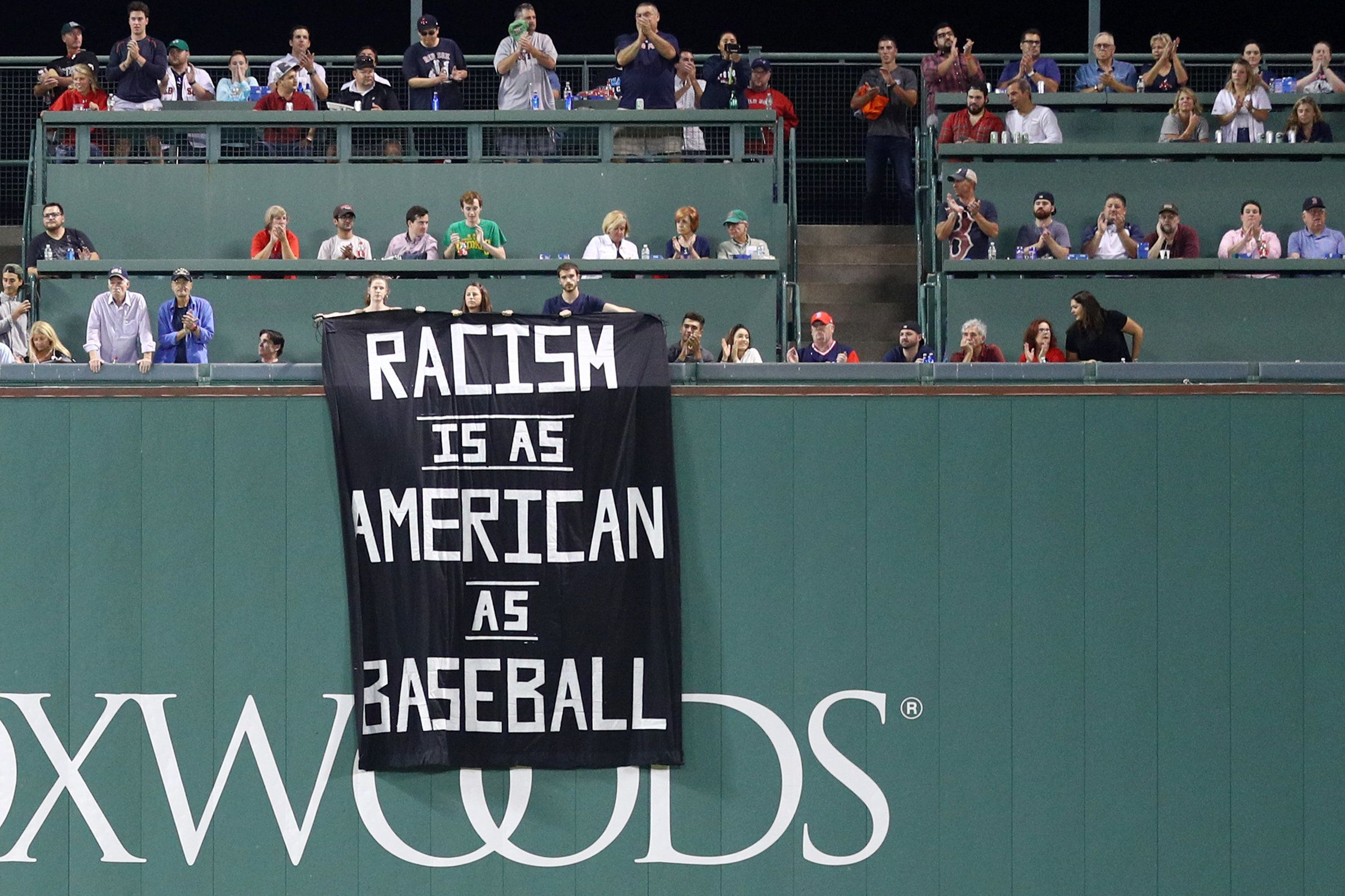 BOSTON, MA - SEPTEMBER 13: A banner with the message 'Racism is as American as baseball' is draped over the Green Monster during the fourth inning of the game between the Boston Red Sox and the Oakland Athletics at Fenway Park on September 13, 2017 in Boston, Massachusetts. (Photo by Maddie Meyer/Getty Images)