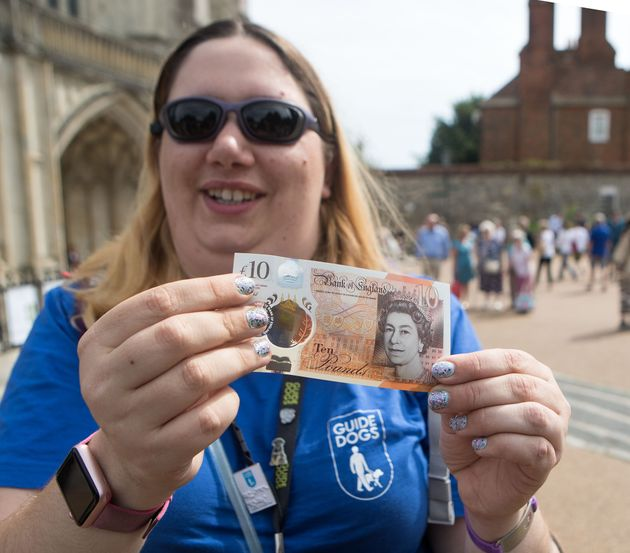 Jemma Brown, from the Guide Dogs association, tests the brail on the new £10