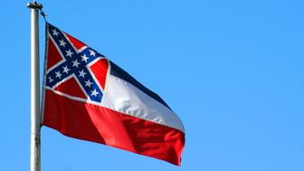 The state flag of Mississippi flying against a blue sky.