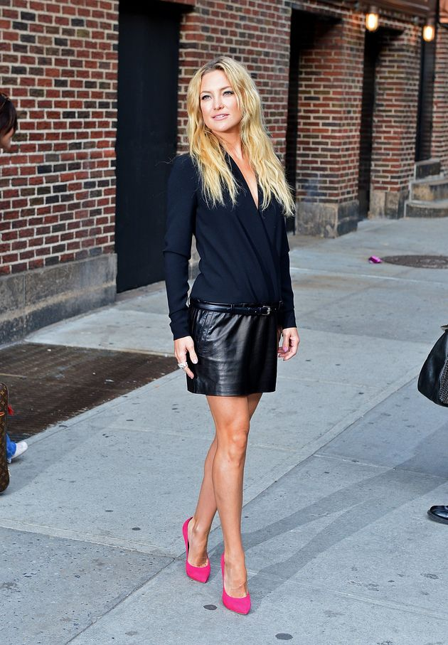 Kate Hudson wearing a navy top and leather skits at the