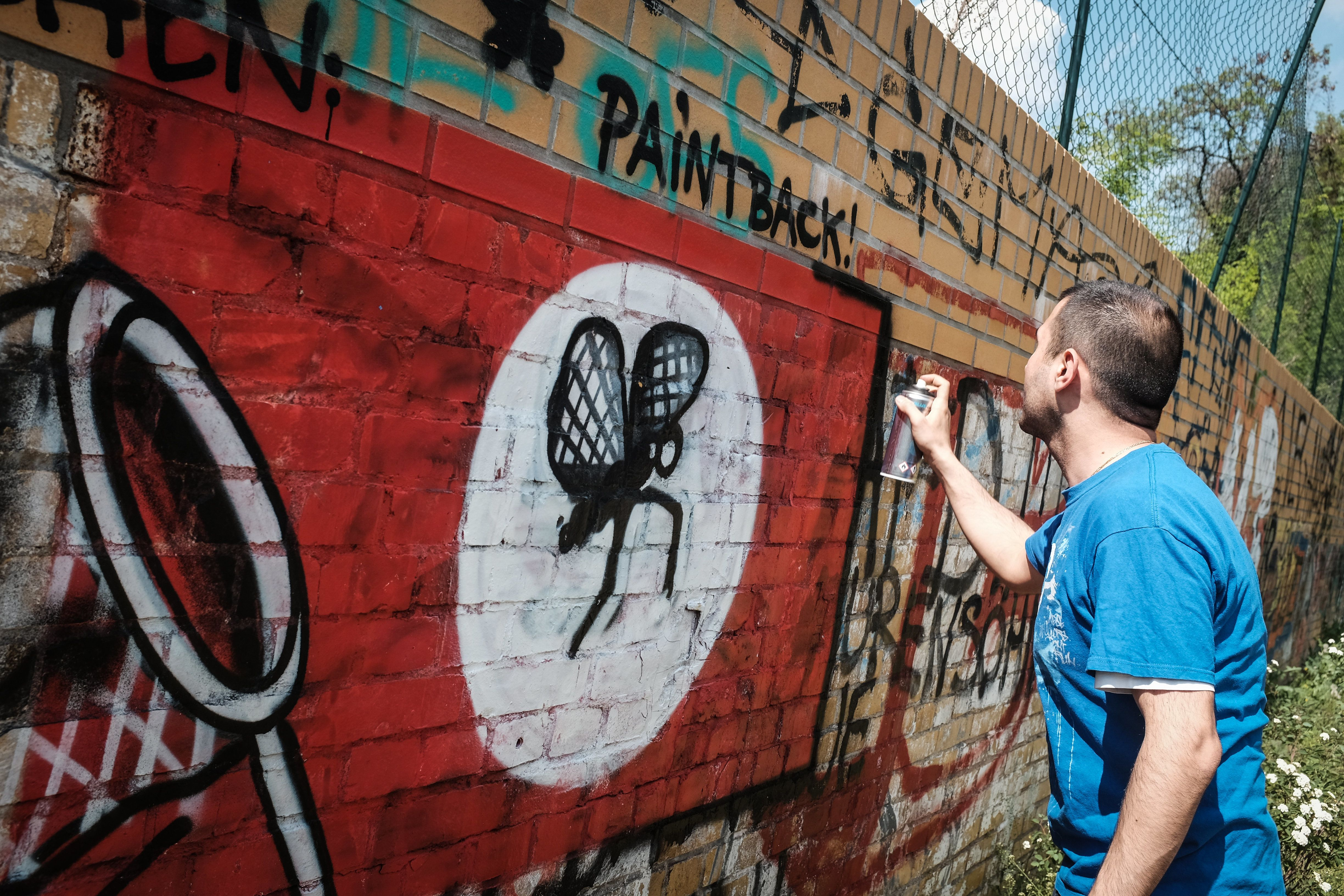 Picture taken on May 11, 2016 shows street artist Ibo Omari overpainting a swastika in Berlin. A ragtag band of Berlin street artists is taking aim at an urban scourge of neo-Nazi graffiti, using 'love and humour' to turn swastikas into colourful symbols of inclusiveness. / AFP PHOTO / dpa / Sophia Kembowski / RESTRICTED TO EDITORIAL USE - MANDATORY MENTION OF THE ARTIST UPON PUBLICATION - TO ILLUSTRATE THE EVENT AS SPECIFIED IN THE CAPTION///TO GO WITH AFP STORY BY OCEANE LAZE AND DEBORAH COLE        (Photo credit should read SOPHIA KEMBOWSKI/AFP/Getty Images)