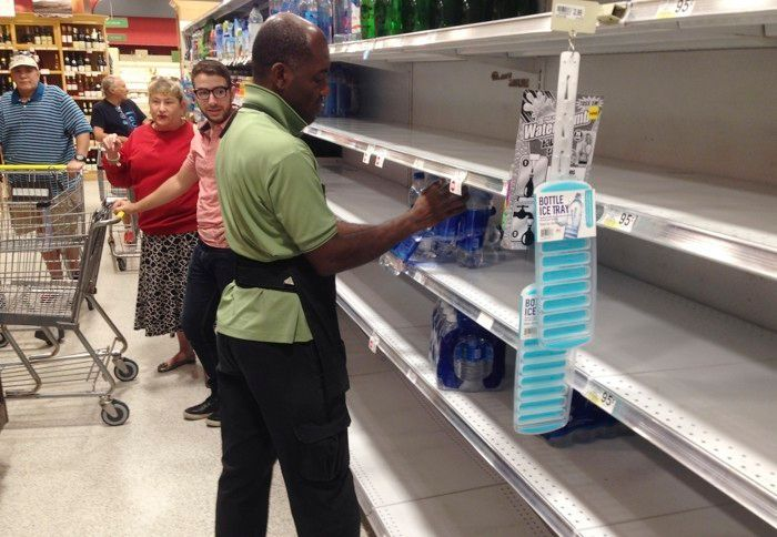 <p>An employee restocks bottled water on bare shelves as customers wait for him at a Publix grocery store on September 5, 2017. </p>