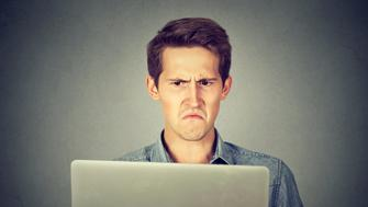 Frustrated disgusted young man looking at his laptop displeased with email