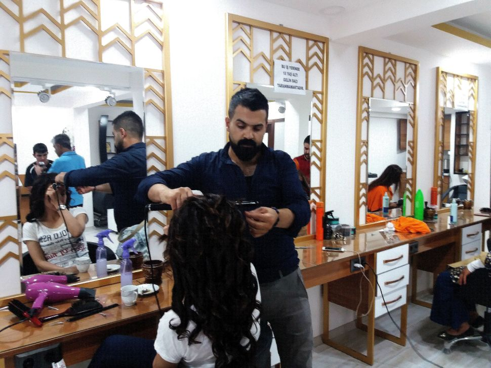 "At Ali İncili's hair salon, a sign on the mirror reads, ""In our premises, we do not offer hairdressing services to"