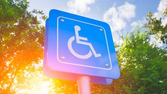 Parking for disability persons sign with green and sun light background.