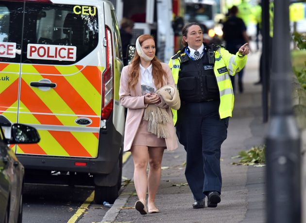 An injured woman is assisted by a police officer close to Parsons Green