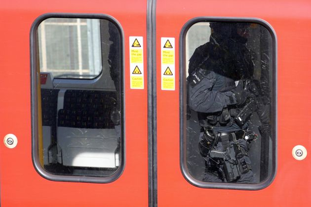 Armed police officers walk through a carriage on the train