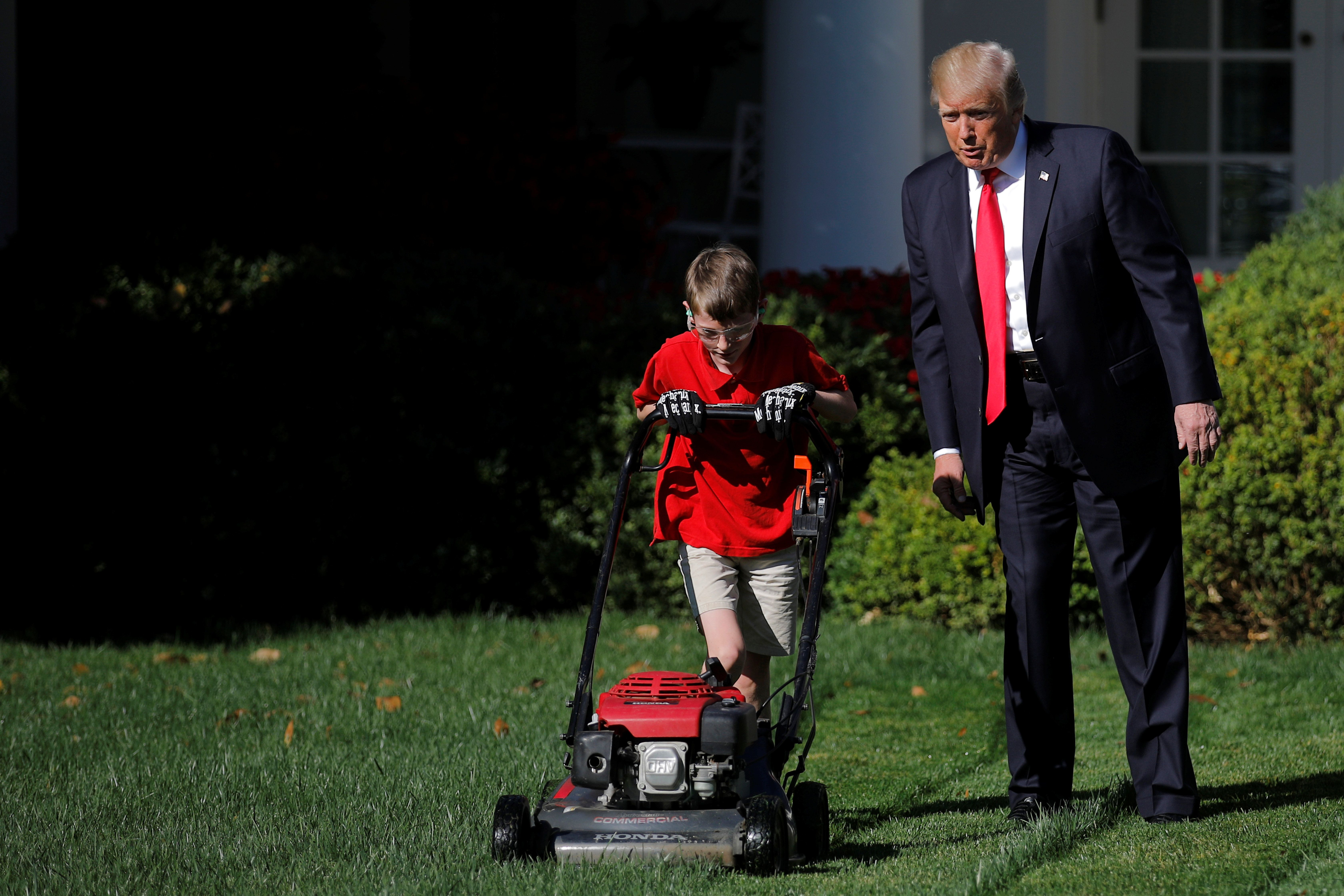 U.S. President Donald Trump looks on as 11-years-old Frank Giaccio cuts the Rose Garden grass at the White House in Washington, U.S., September 15, 2017. Frank, who wrote a letter to Trump offering to mow the White House lawn, was invited to work for a day at the White House along the National Park Service staff. REUTERS/Carlos Barria