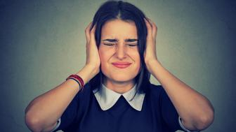 Stressed frustrated woman covering her ears with hands isolated gray background. Negative human emotion reaction attitude