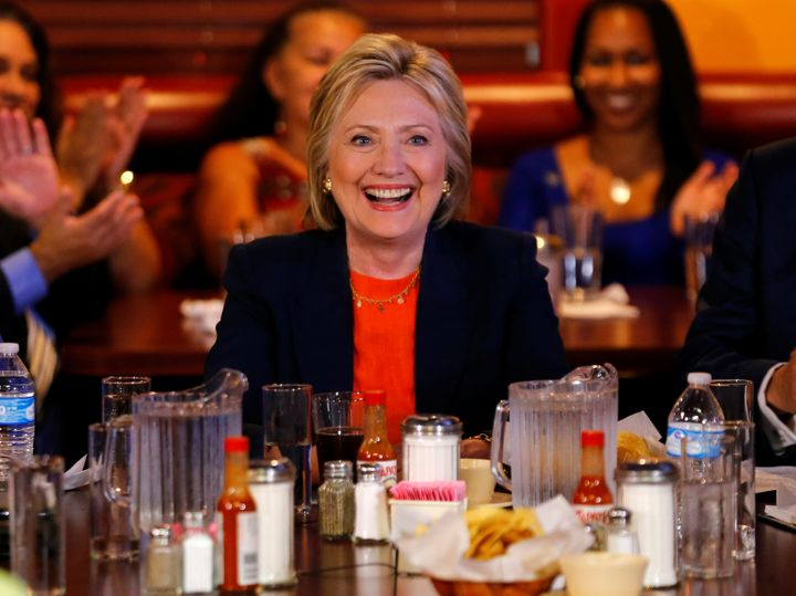 Clinton smiles amid hot sauce bottles while making a campaign stop at a restaurant in Perris, California on June 2, 2016