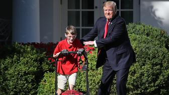 WASHINGTON, DC - SEPTEMBER 15:  11-year-old Frank 'FX' Giaccio (L) gets a pat on the back from U.S. President Donald Trump (C) while mowing the grass in the Rose Garden of the White House September 15, 2017 in Washington, DC. Giaccio, from Falls Church, Virginia, who runs a business called FX Mowing, wrote a letter to Trump expressing admiration for Trump's business background and offered to mow the White House grass.  (Photo by Win McNamee/Getty Images)