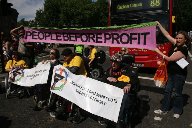 The group, Disabled People Against Cuts, block the road outside Westminster