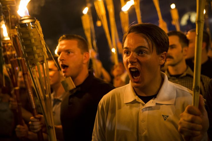 Neo-Nazis and white supremacists hold torches and chant at counter-protesters after marching through the University of Virgin