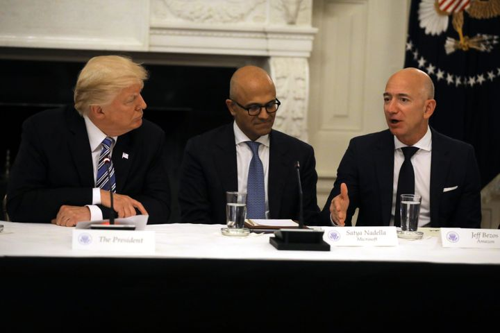 Washington Post owner Jeff Bezos, right, speaks during a meeting with President Donald Trump on June 19, 2017, alongside Micr