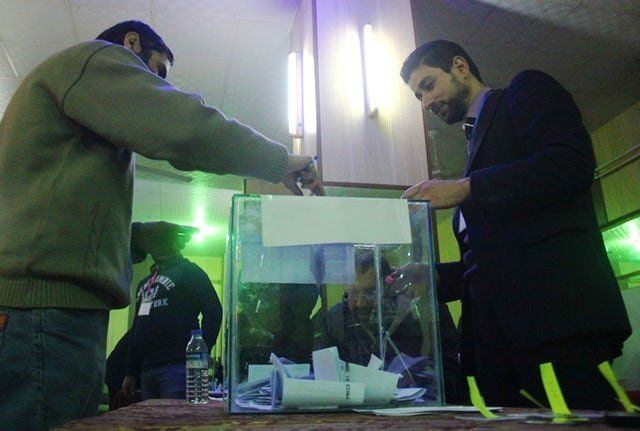 A Syrian man casts his vote in a ballot box at a polling station in the city of Idlib as the city's first civilian coun