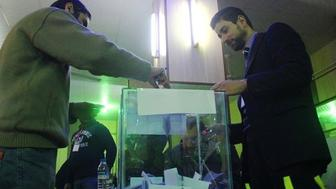 A Syrian man casts his vote in a ballot box at a polling station in the city of Idlib as the citys first civilian council is elected two years after it was overrun by rebels and jihadists on January 17 2017