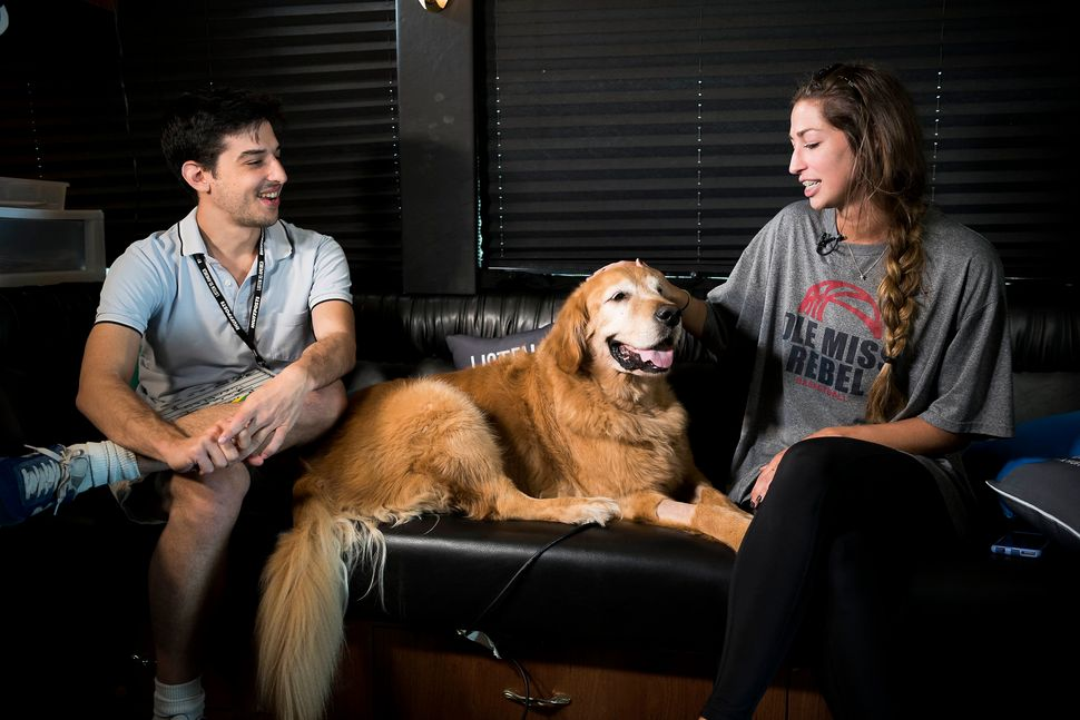 Sam Levine interviews Julia Tatum while her dog Bentley sits on the couch with them inside the HuffPost tour bus.
