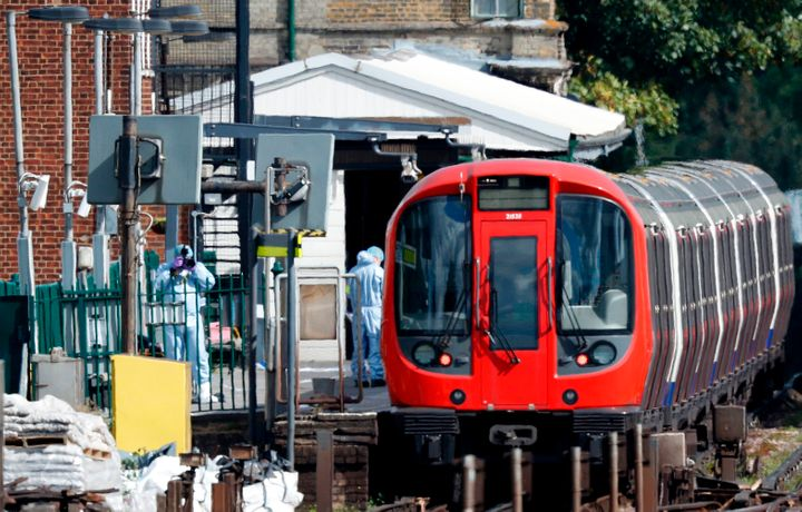 Police forensics officers works alongside an underground tube train at a platform at Parsons Green underground tube station i
