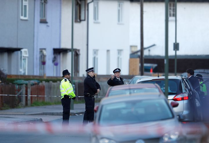 Police officers stand behind cordon tape near a property that was searched after a man was arrested in connection with an exp
