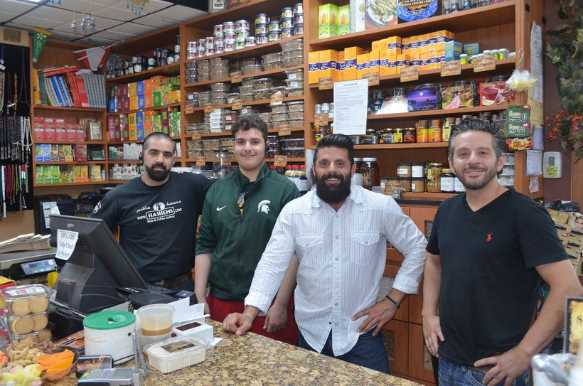 From right to left, Wessam Hashem, Adam Hashem and several of the workers at Hashem's Nuts & Coffee Gallery offering high