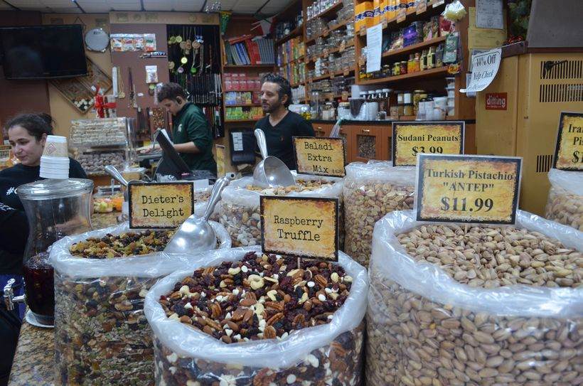 "At ""Hashem's Nuts & Coffee Gallery"" a variety of mixed nuts is on display, inviting the customer to dive in and try their"