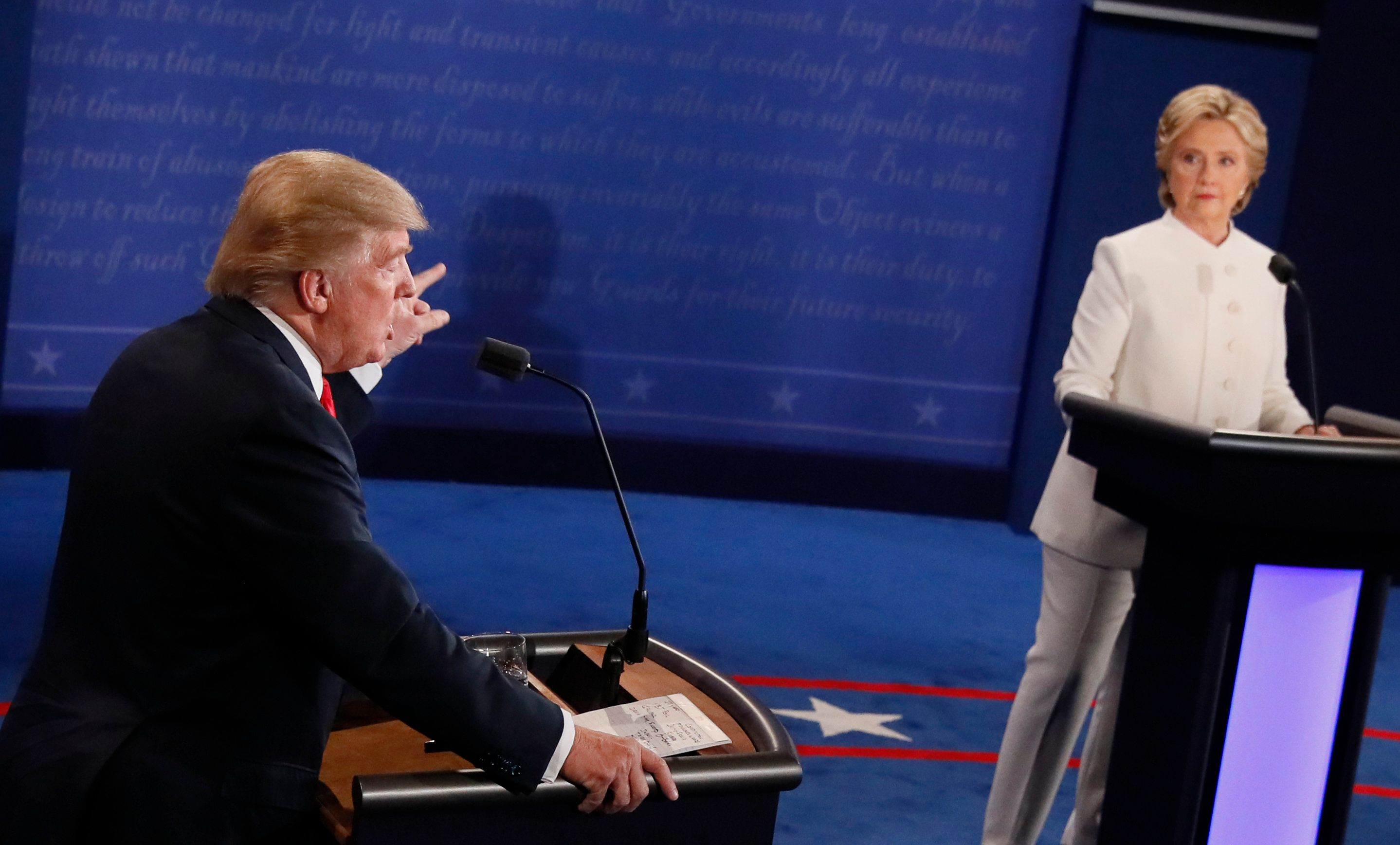 Then-Republican presidential nominee Donald Trump speaks as then-Democratic presidential nominee Hillary Clinton looks on dur