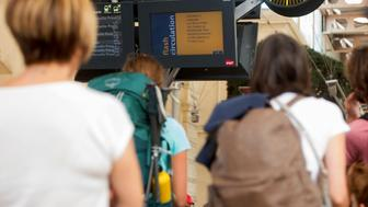 Passengers look at information monitors as they wait for their trains at The Saint-Charles Station in Marseille on August 20, 2017, following a fire between Aubagne and Carnoux, south-eastern France.  Holidaymakers who were staying near Aubagne were momentarily evacuated on the night of August 19 and residents confined to their homes as a wildfire burned through 200 hectares of vegetation. Some 3,000 travellers in southern France spent thenight camped out in train stations after a bush fire cut off a busy route between Marseille and the resort city of Nice. / AFP PHOTO / BERTRAND LANGLOIS        (Photo credit should read BERTRAND LANGLOIS/AFP/Getty Images)