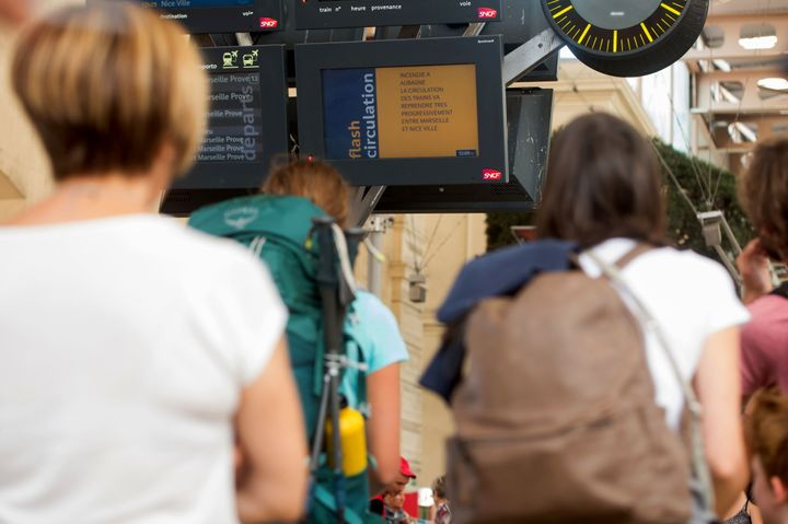 Passengers look at information monitors as they wait for their trains at The Saint-Charles Station in Marseille on August 20,