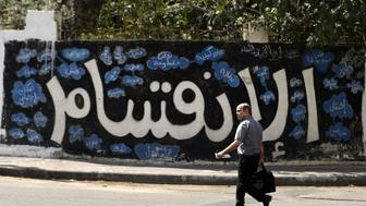 A Palestinian man walks past a graffiti reading in Arabic ''Division'' in Gaza City, on September 17, 2017, after Hamas announced it had agreed to steps toward resolving a decade-long split with the Fatah movement and was ready to hold elections. Hamas said it had agreed to key demands made by Fatah: dissolving the so-called 'administrative committee', while saying it was ready for elections and negotiations toward a unity government. / AFP PHOTO / MAHMUD HAMS        (Photo credit should read MAHMUD HAMS/AFP/Getty Images)