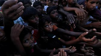People reach out during the distribution of bananas in a Rohingya refugee camp in Cox's Bazar, Bangladesh, September 17, 2017. REUTERS/Cathal McNaughton
