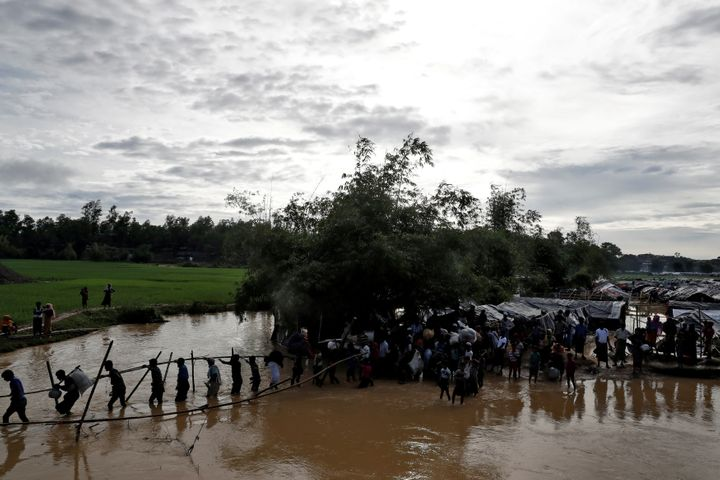 Rohingya cross a swollen river at a refugee camp in Cox's Bazar, Bangladesh, September 17, 2017.
