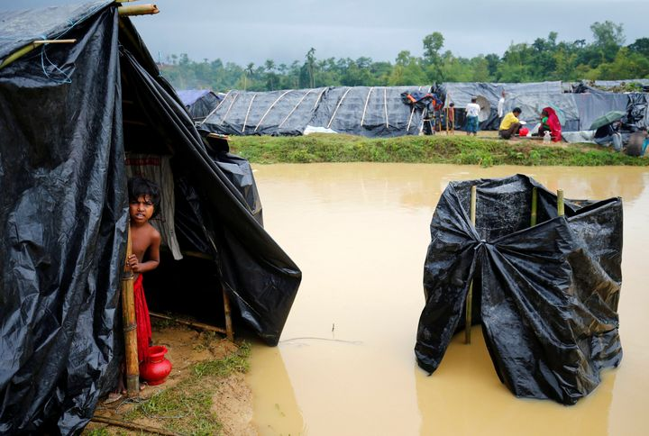 A Rohingya refugee girl looks out as makeshift shelters become flooded due to heavy rain in Cox's Bazar, Bangladesh, Septembe