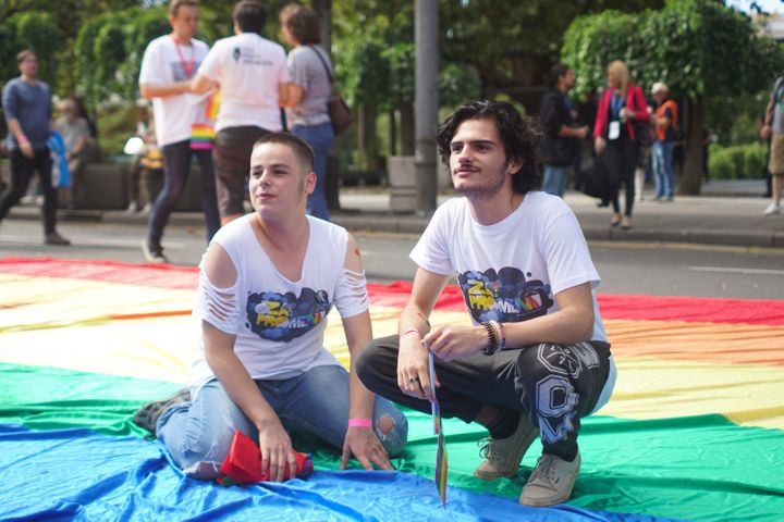 Boys posing for a photo on a gigantic rainbow flag.